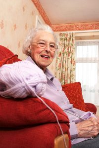 Lady Knitting on the Sofa in her home